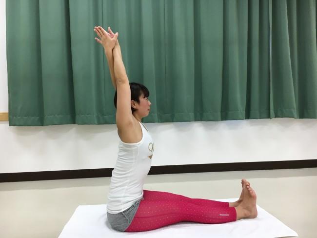 床に足を伸ばて座り、腕をバンザイに。右手の掌は右外へ向け、左手の掌は左外へ向ける。そして腕をからめるように両手の掌を合わせる。