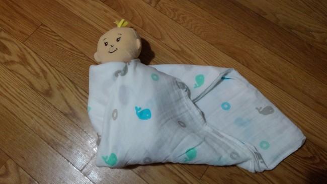 ③下に余ったおくるみをまとめるように軽く巻きながら、赤ちゃんの左肩まで持って行き、先端を背中の下に入れ込みます