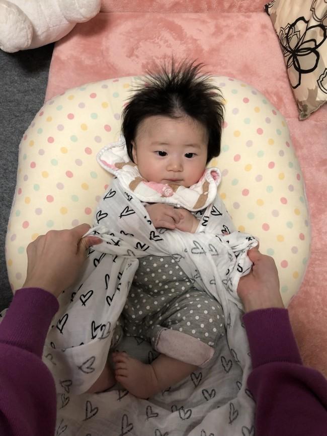 赤ちゃんの肘を支えながら、手の下で布の両端を2回しっかり結びます。まだ手遊びしない赤ちゃんなら、首のすぐ下で結んでしまってもOK。きつく結んで、苦しくならないように