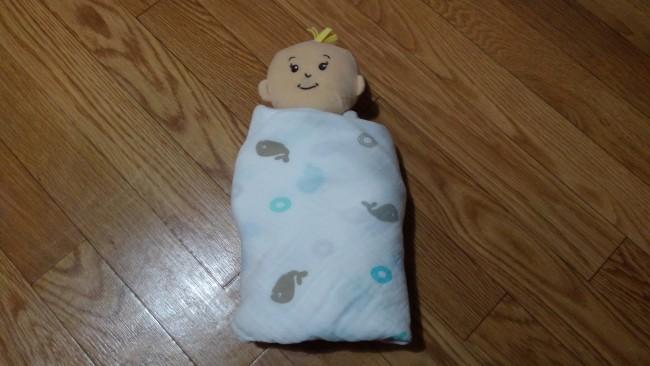 ④反対側の腕も真っ直ぐ下に伸ばし、赤ちゃんの左側のおくるみを持ち上げて赤ちゃんに巻きます。おくるみの布がなくなるまで、ぐるっと1周ほど巻きつけて、完成です