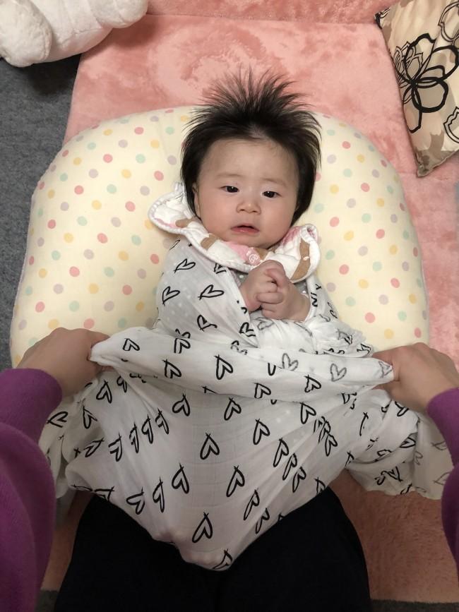 ママの膝で赤ちゃんのお尻を支えながら、赤ちゃんの足をあぐらか、裏を合わせて下の布を被せ、下半身をしっかりくるめるようにします