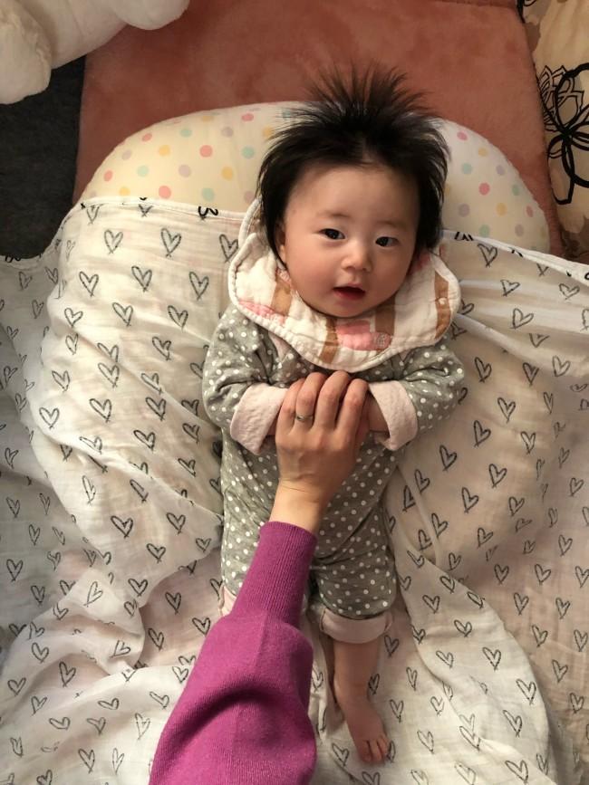おくるみの中央部に赤ちゃんをのせ、まず、耳の少し下辺りにおくるみの端が来るように広げます。両手を優しく持ってあげましょう