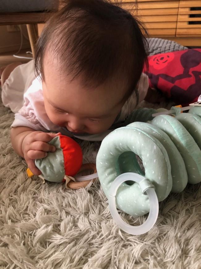 首すわりの練習もかねて床に置いてみると、おもちゃで遊びながら集中!