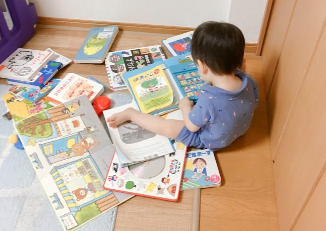部屋の角にお気に入りの絵本を運んで歌を選んでいます