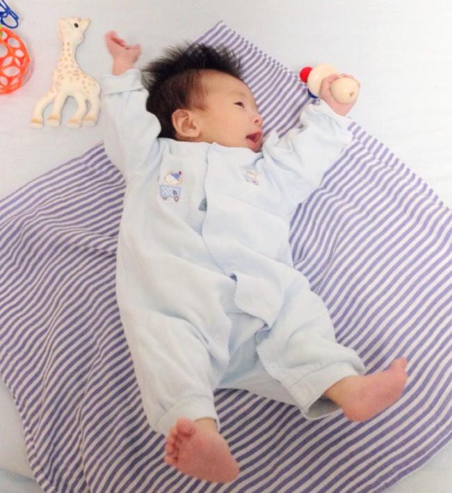 鮮やかな色のおくるみの上で撮影することで赤ちゃんが背景よりも鮮やかになるので、動きが鮮明になります