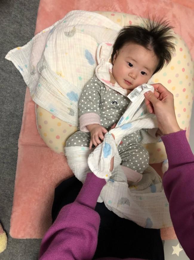 肩側の端と、対角線上の端を、赤ちゃんのお尻をすっぽり包み込むような形で結びます