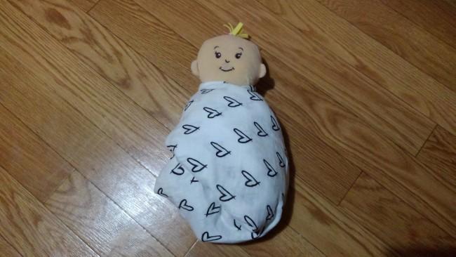 ⑤また同じように、余った赤ちゃんの左側のおくるみも、赤ちゃんの肩まで持って行き、肩の下に入れ込みます。ぴったりと巻かれていることと、赤ちゃんの呼吸が妨げられていないことを確認して、完成です