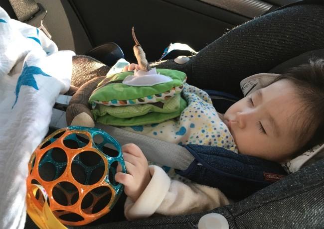 おもちゃを抱えたまま寝てしまったので、上からおくるみをかけてあげました