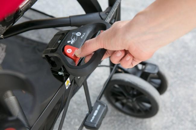 シートの背面にある車体収納ハンドルを持ち、赤いボタンを押しながらハンドルを引っ張るだけ