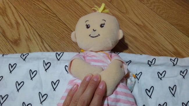 ①おくるみを四角い状態に広げます。長方形のおくるみやベビー用バスタオルを使う時には、横長にして置きましょう。赤ちゃんの顔だけがおくるみから出るようにして、おくるみの上に寝かせます。この時両腕は前におさめておくとよいです