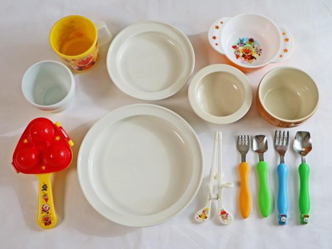 左上からケユカのコップ、レックのアンパンマンコップ、ユニバーサルデザインの小皿、いにま陶房のやさしい器、レックのアンパンマン器、ストウブの器、エジソンのトーマスの付いたカトラリーとデザート用に使っているミニカトラリー、エジソンのお箸、ユニバーサルデザインのお皿、レックのおにぎりメーカー