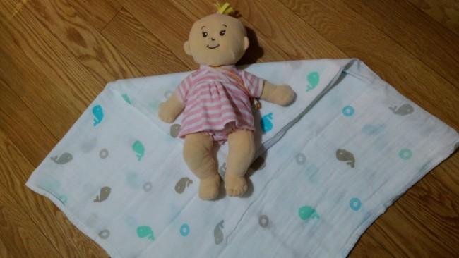 ①おくるみをひし形に置き、上の角を真ん中くらいまで、内側に折り込みます。赤ちゃんの肩を折り目と合わせるように、おくるみの上に寝かせます