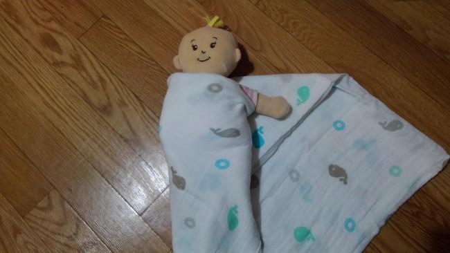 ②赤ちゃんの右腕を真っ直ぐ下に伸ばし、向かって左側のおくるみを持ち上げて赤ちゃんの体の右側に巻きつけます