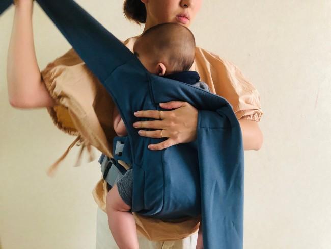 子どもの背中に合わせて背当て部分をかぶせたら、肩ストラップを反対方向の脇に向けてひょいっとうしろへ