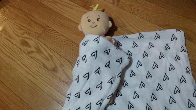 ②赤ちゃんの右側のおくるみを左側に斜めに持って行きます。その際、赤ちゃんの右腕は、真っ直ぐ伸ばしてからだに密着させておきます。おくるみの端は赤ちゃんの肩に入れ込みましょう